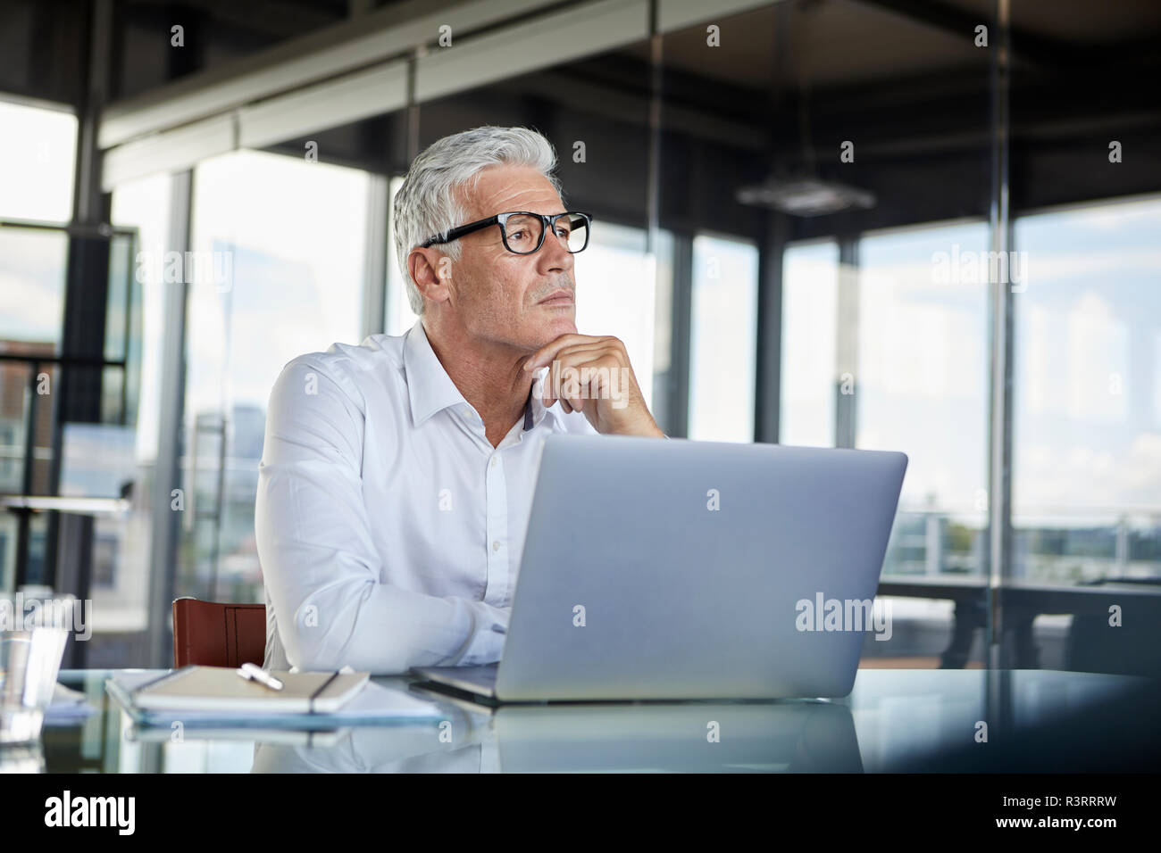 Businessman sitting in office, thinking Stock Photo