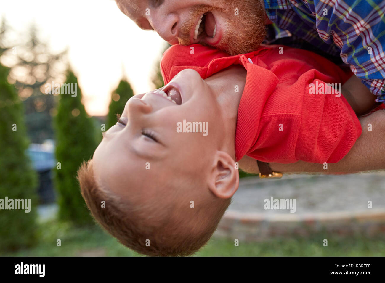 Happy playful father with his son in garden Stock Photo