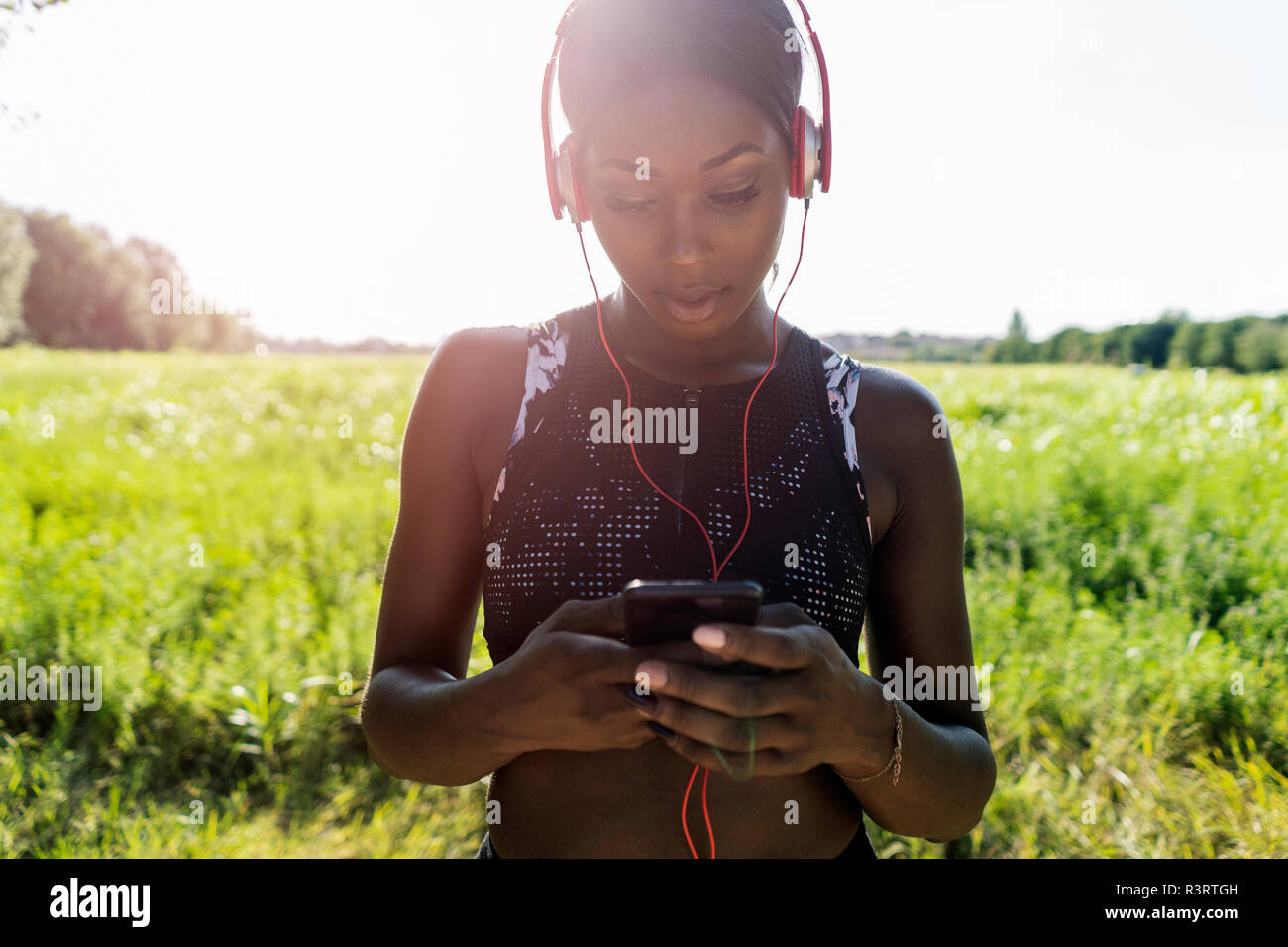 Young athlete in nature, listening music with headphones, holding smartphone - Stock Image