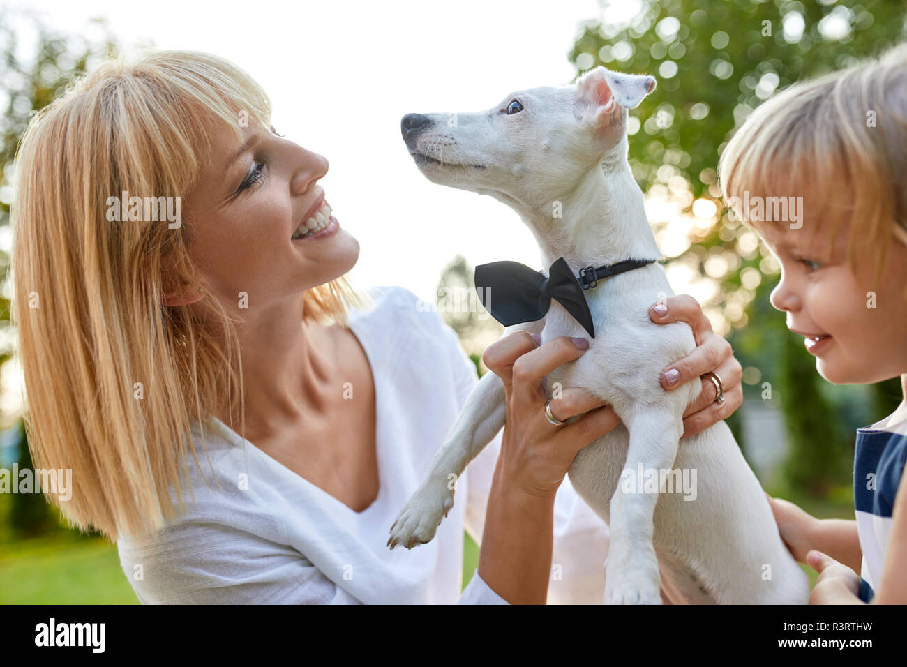 Happy woman with daughter holding dog wearing a bowtie outdoors - Stock Image