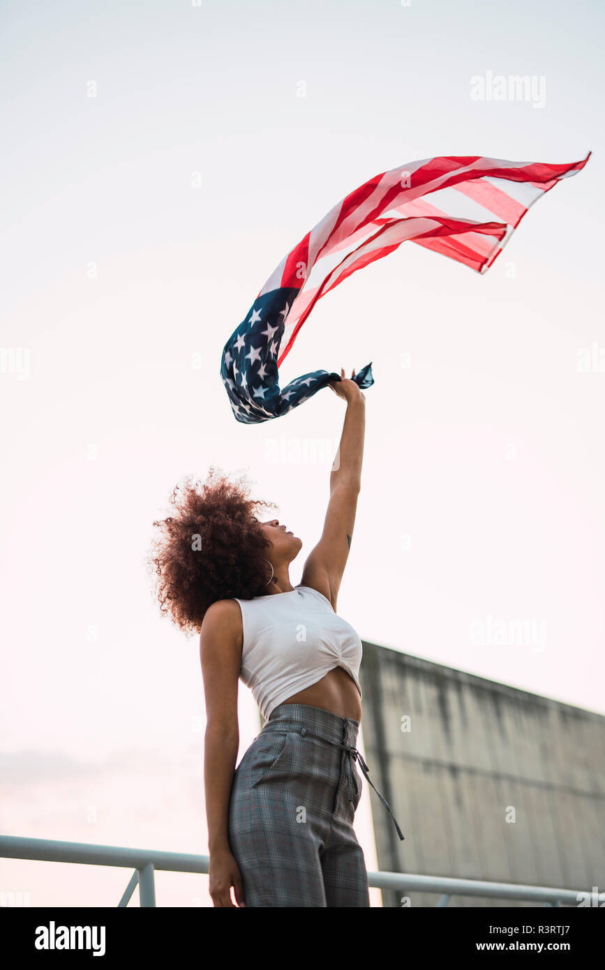 Young woman swinging American flag - Stock Image