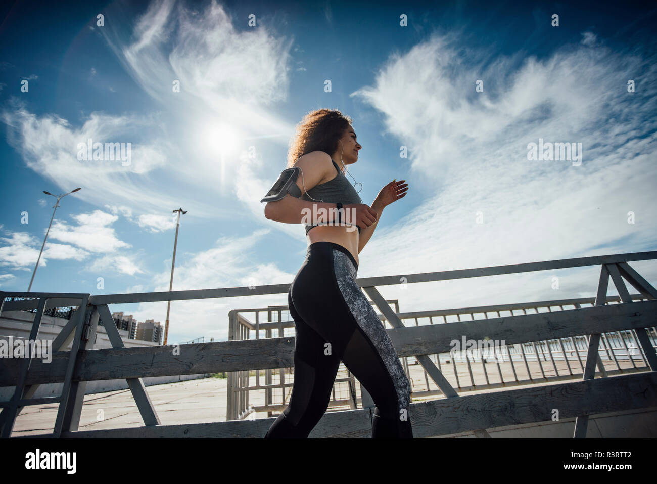 Young athletic woman running on a pier - Stock Image