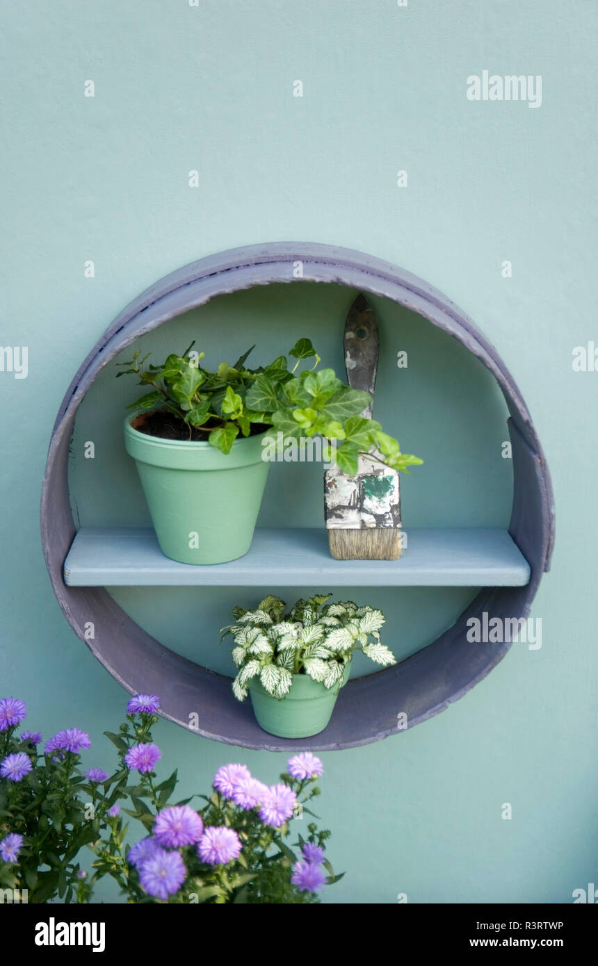Flower decoration, flour sifter, shelf, brush, flower pots with ivy and aster - Stock Image