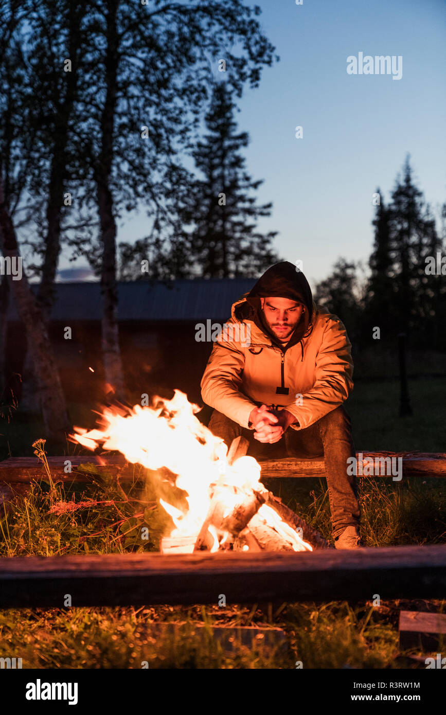 Young man sitting at a campfire, watching the flames - Stock Image