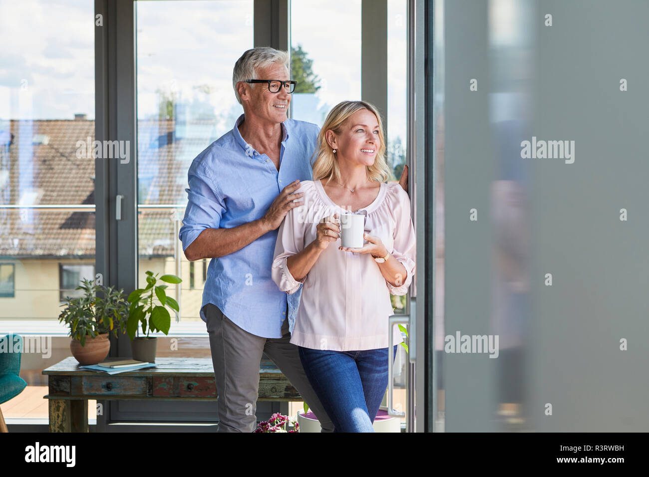 Smiling mature couple relaxing at home looking out of window Stock Photo
