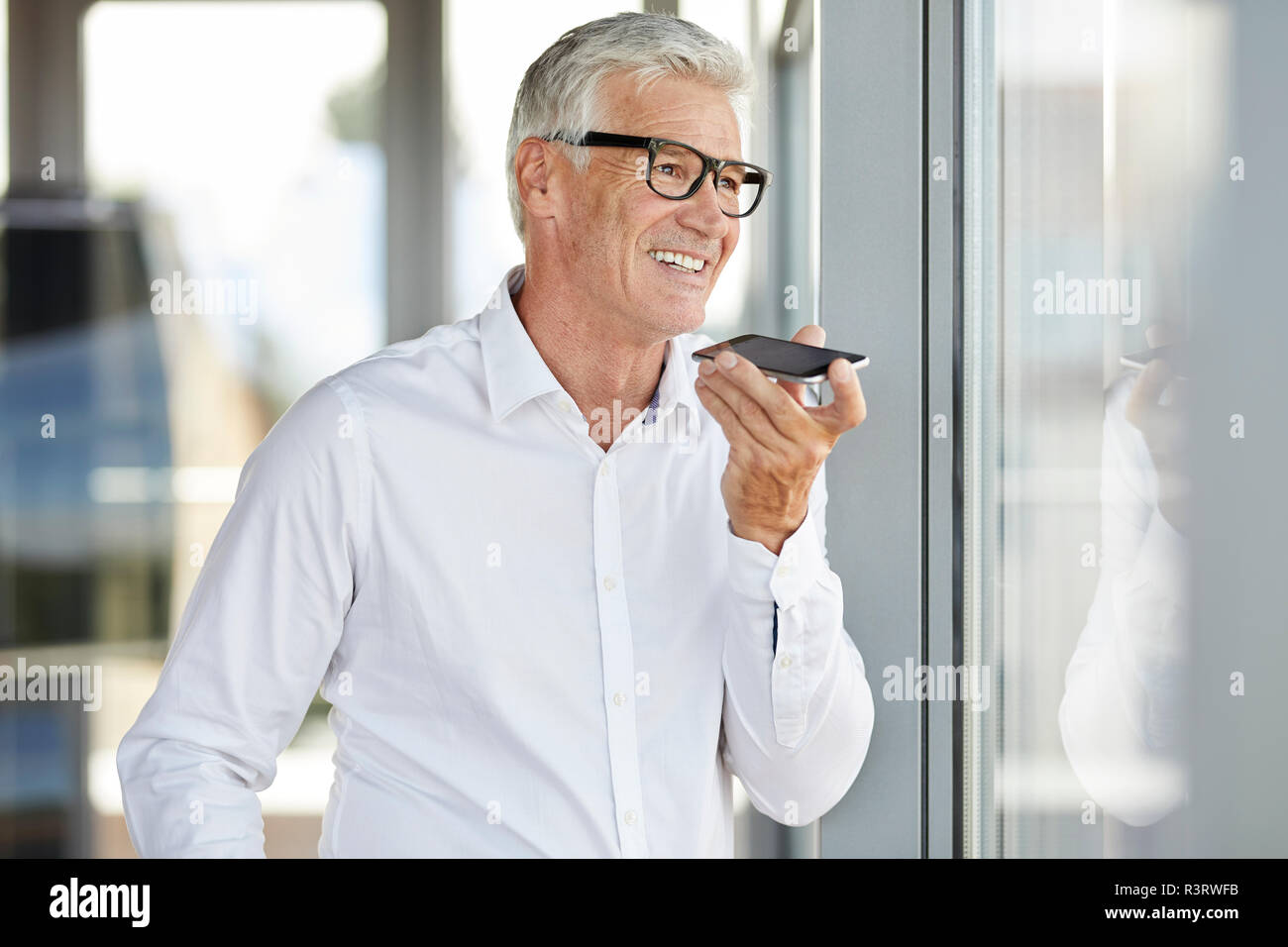 Successful businessman using smartphone, leaving voice mail - Stock Image