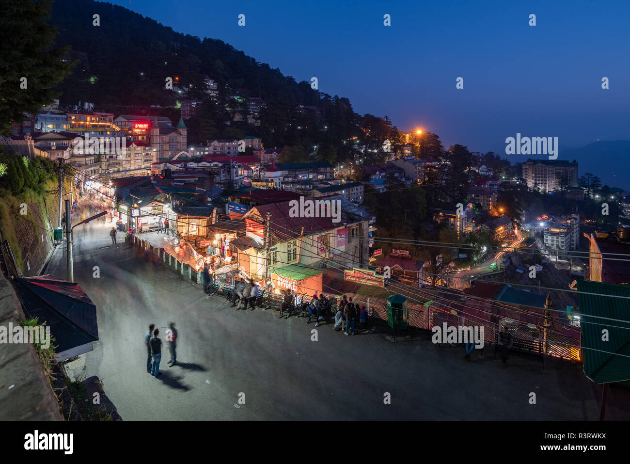 A group of three people stopped to have a chat on the busy Mall Road in Shimla at night, Himachal Pradesh, India - Stock Image