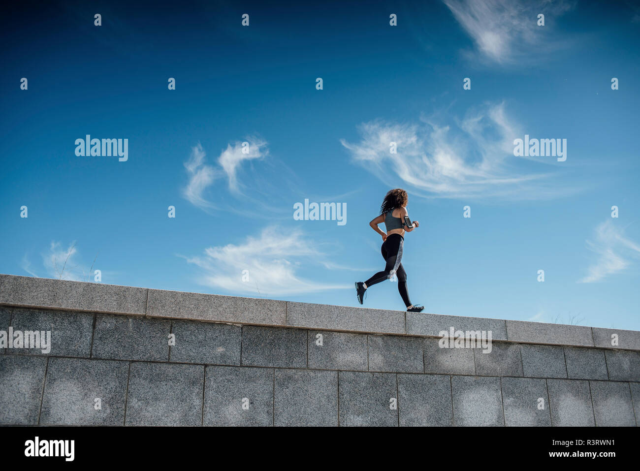 Young athletic woman running on a wall - Stock Image