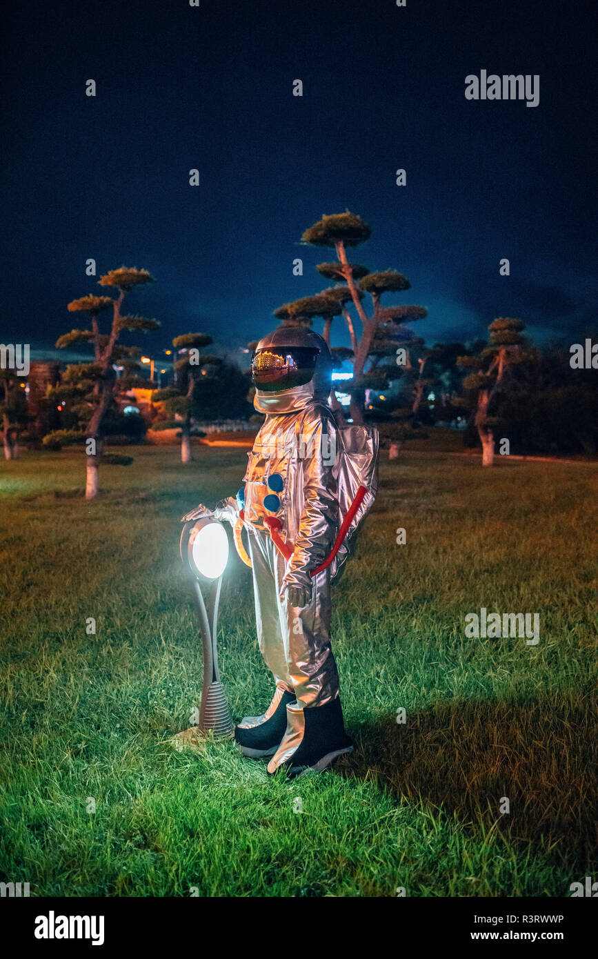 Spaceman standing at a lamp in a park at night - Stock Image