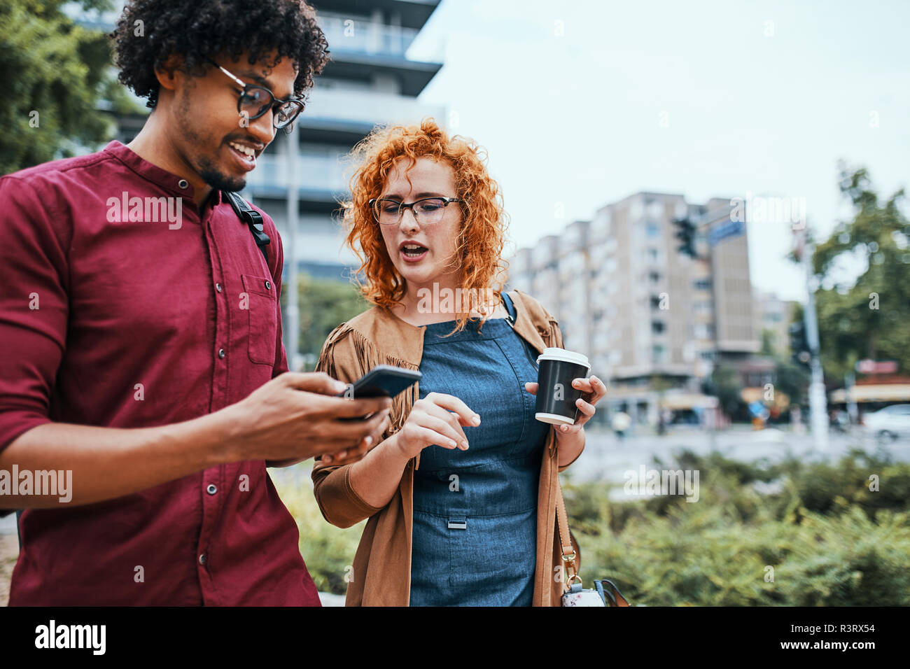Colleagues walking in the city, talking, using smartphone - Stock Image