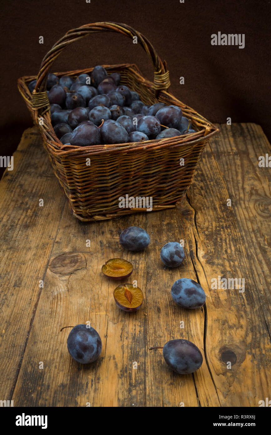 Wicker basket of organic plums, wooden table - Stock Image