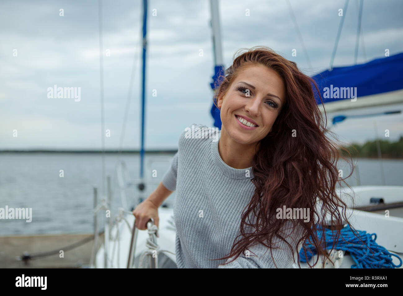 Portrait of woman, having fun on a sailing boat - Stock Image