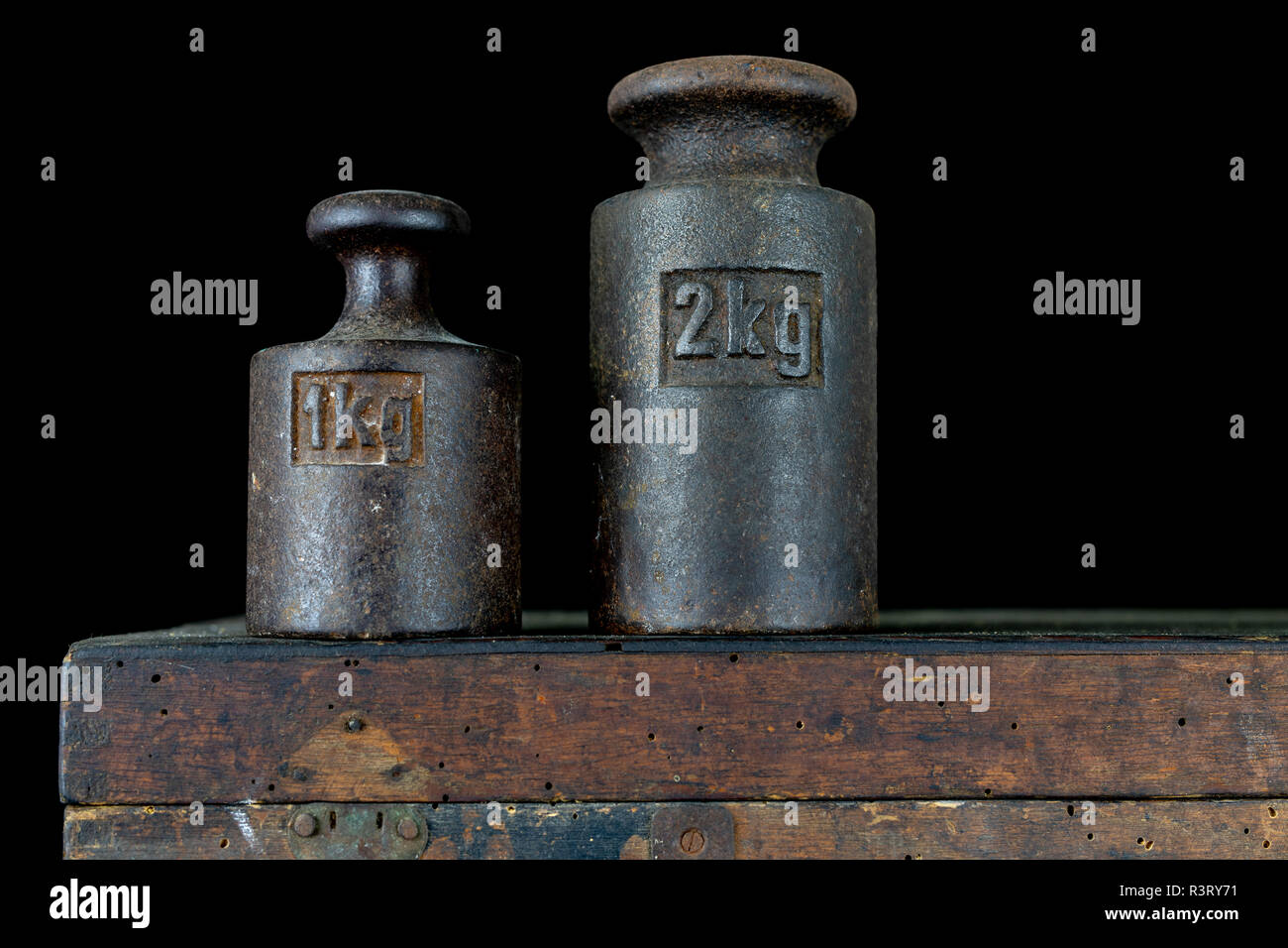 A kilogram weight used for weighing a given quantity in the store. Weights of one kilogram and two kilograms. Dark background. - Stock Image