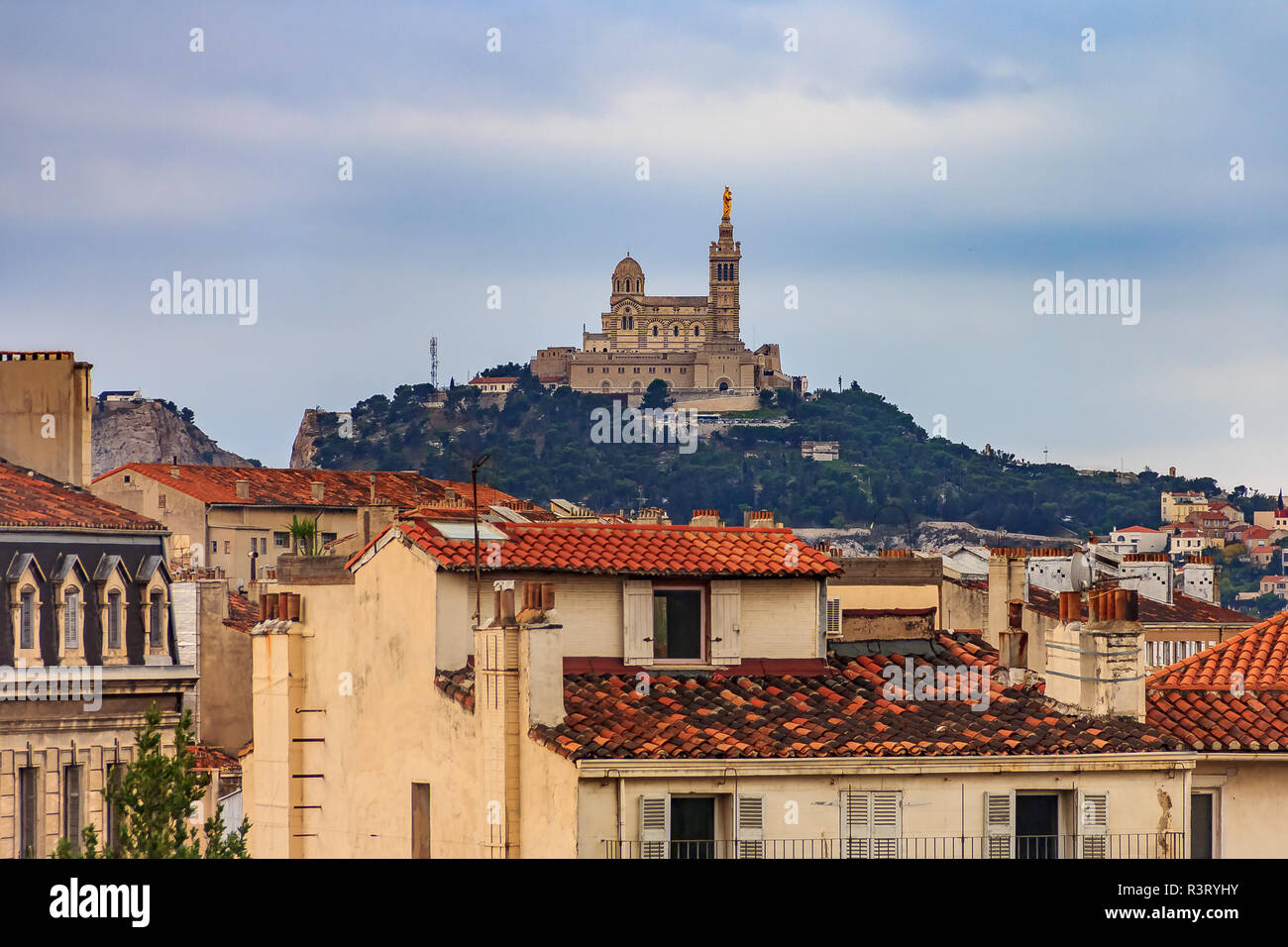 View onto city rooftops and Notre-Dame de la Garde Catholic basilica on the hill, city's best-known symbol and site of a popular Assumption Day pilgri - Stock Image