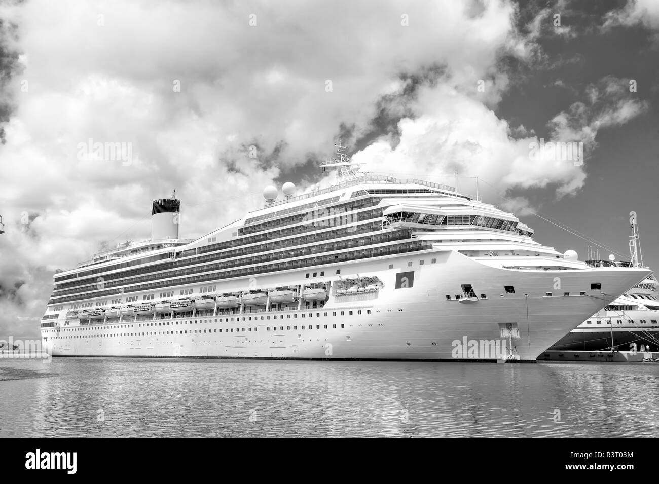 Large luxury cruise ship or liner on sea water and cloudy sky background docked at port of st.Johns, Antigua Stock Photo