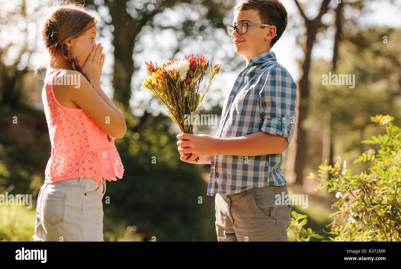 Girl giving boy flowers stock photos girl giving boy - Boy propose girl with rose image ...