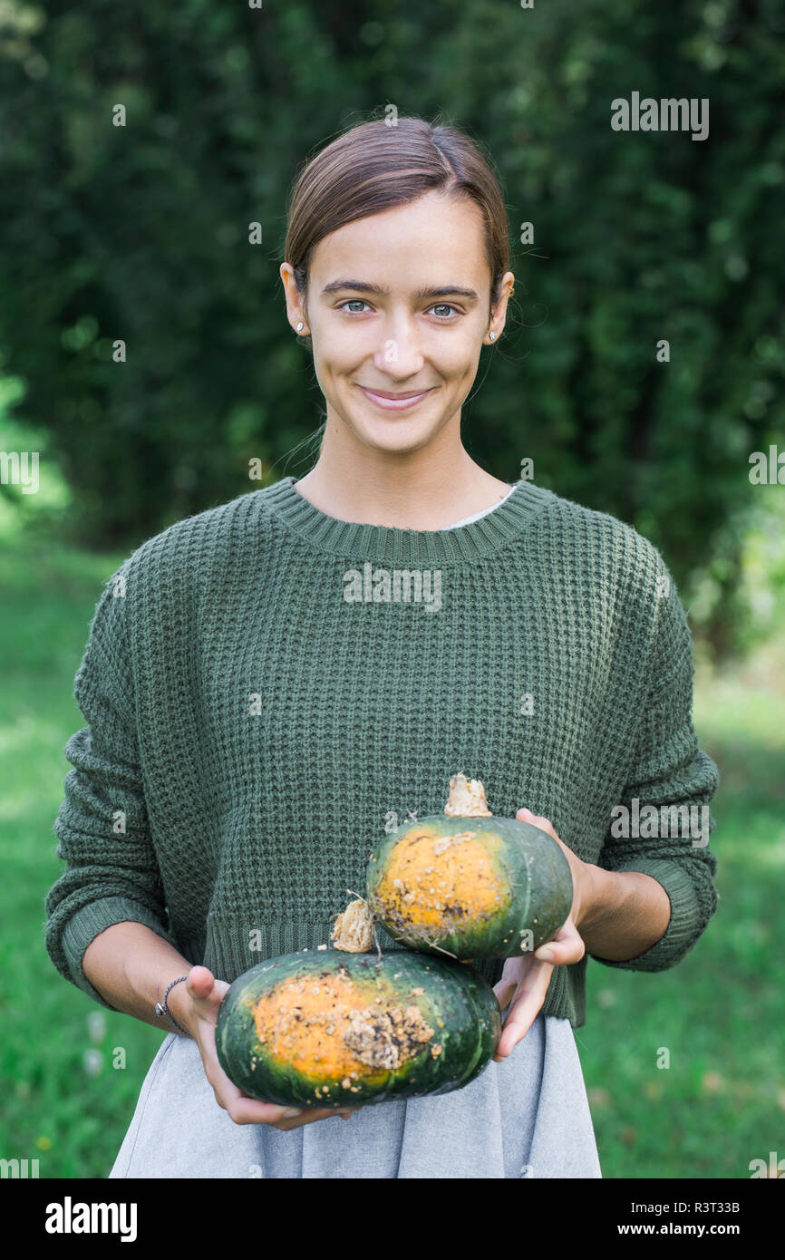 Porrtait of smiling young woman with two pumpkins in the garden - Stock Image