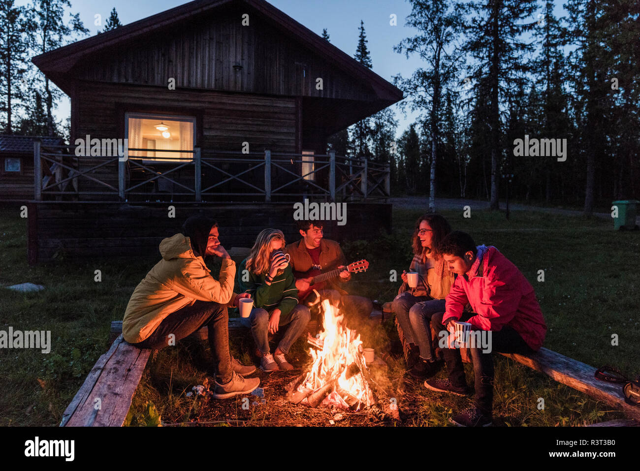 Group of friends sitting at a campfire, talking and playing guitar - Stock Image