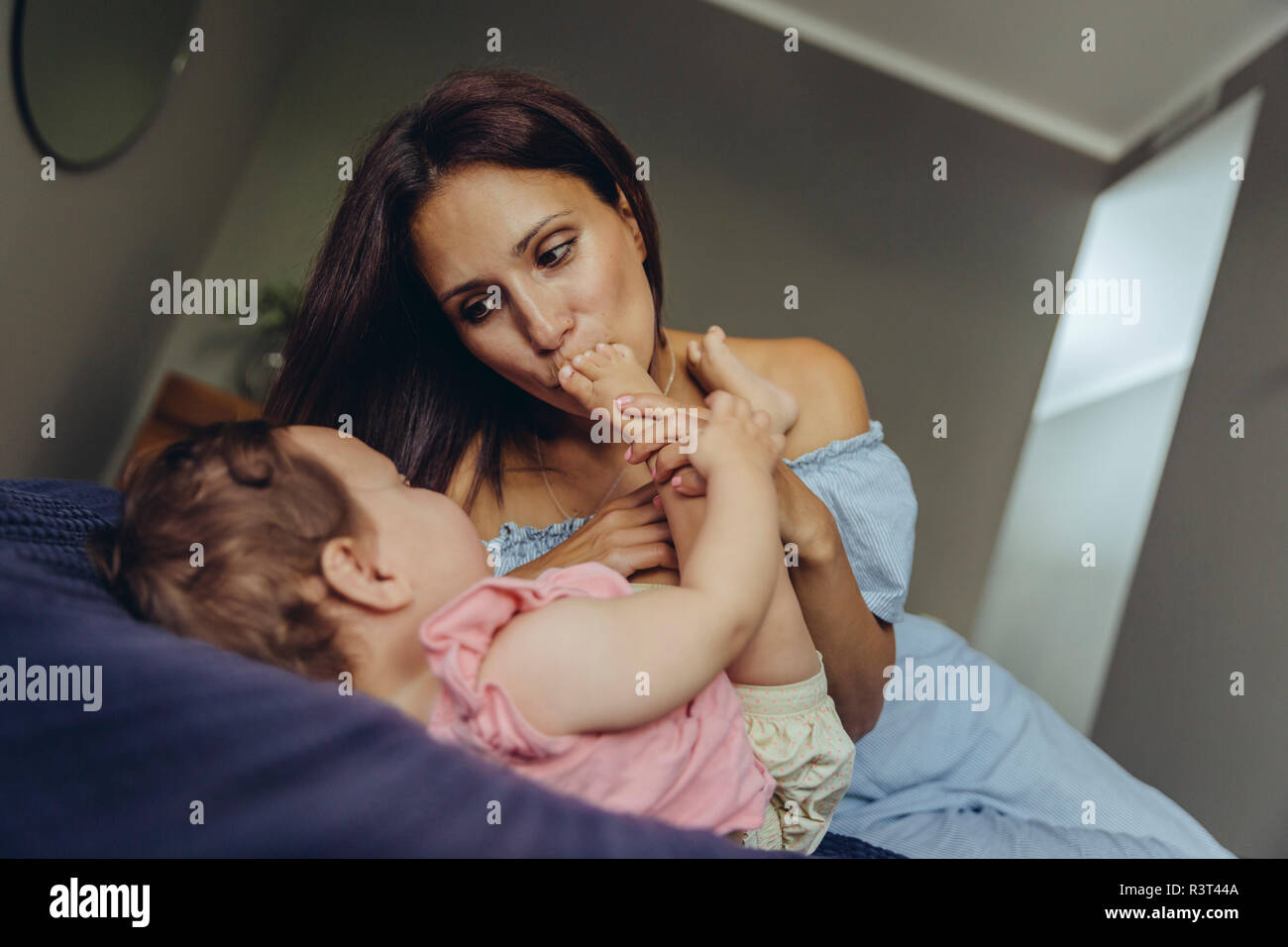 Mother kissing her baby girl's feet on bed - Stock Image