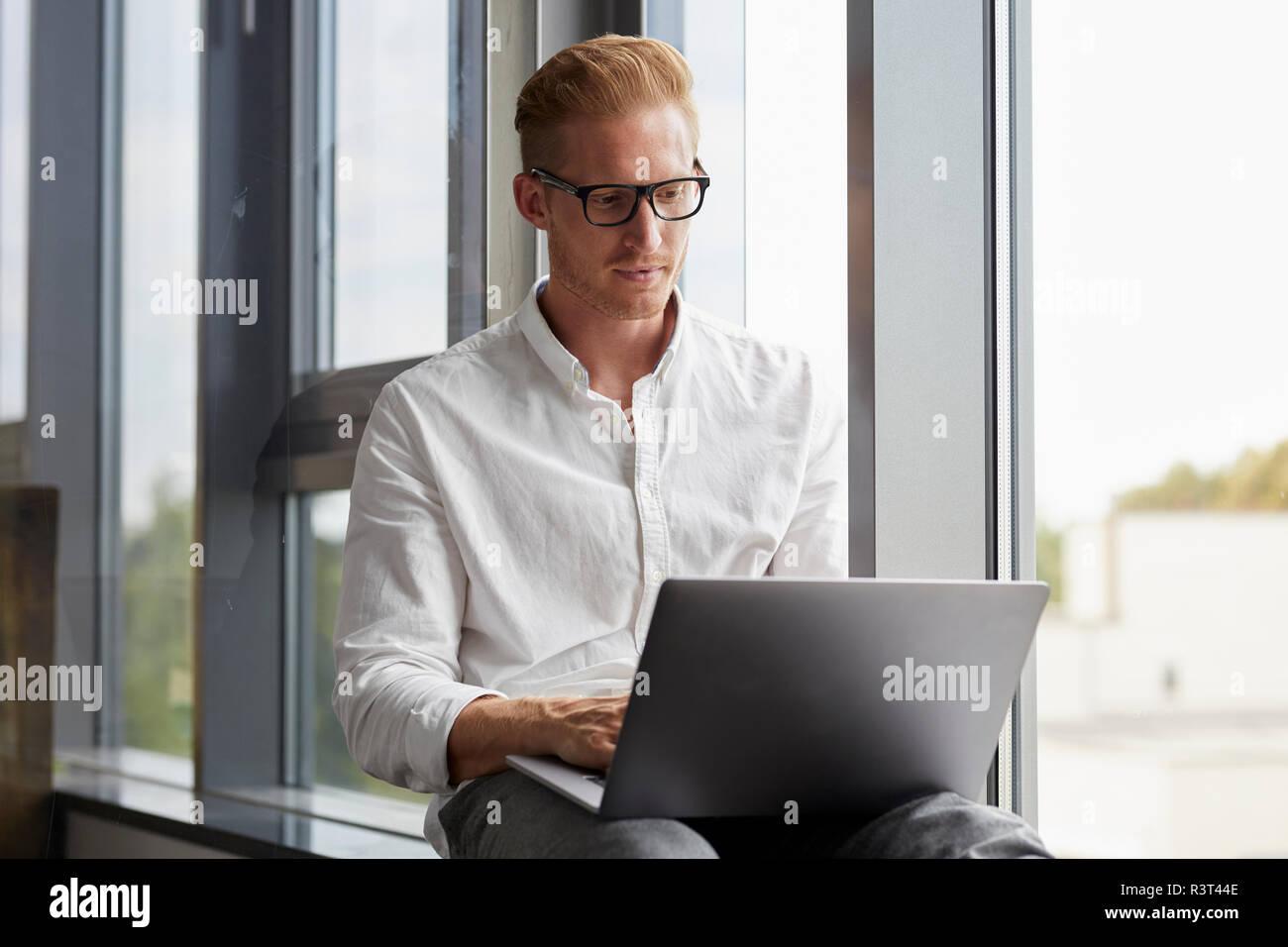 Businessman sitting on windowsill using laptop - Stock Image