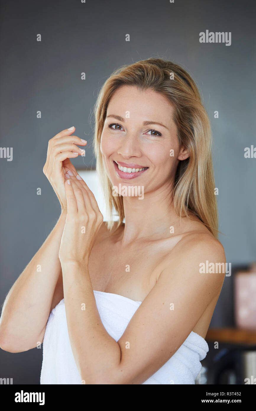 Portrait of smiling blond woman applying face cream in the morning - Stock Image