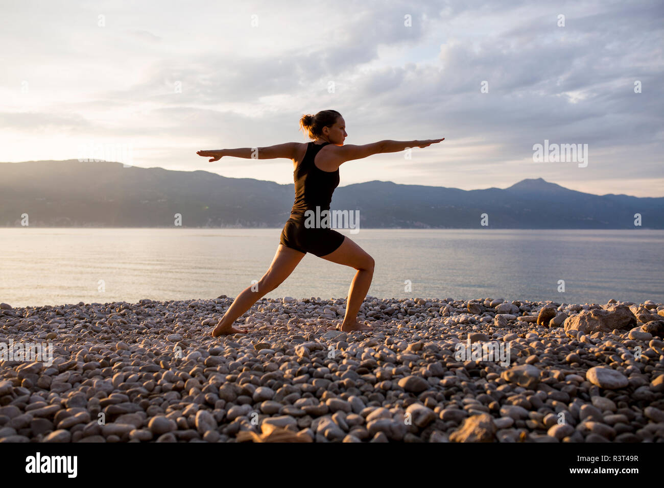 Young woman doing yoga at the stony beach in the evening, Warrior pose Stock Photo