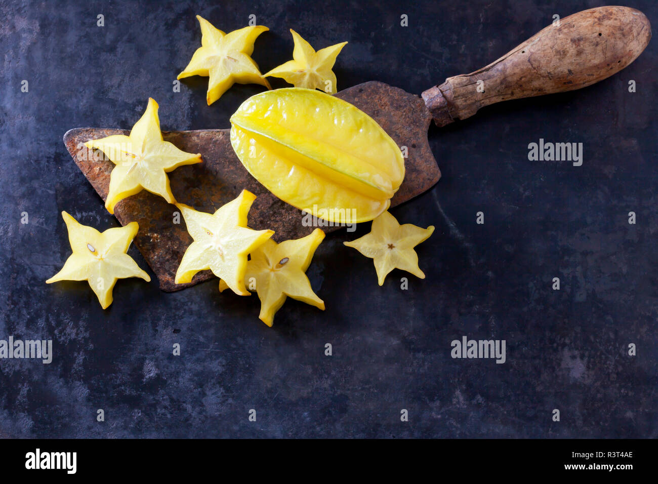 Sliced starfruit on an old cleaver - Stock Image