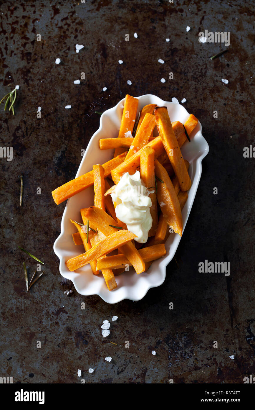 Salted sweet potato fries with rosmary and mayonnaise in porcelain bowl - Stock Image