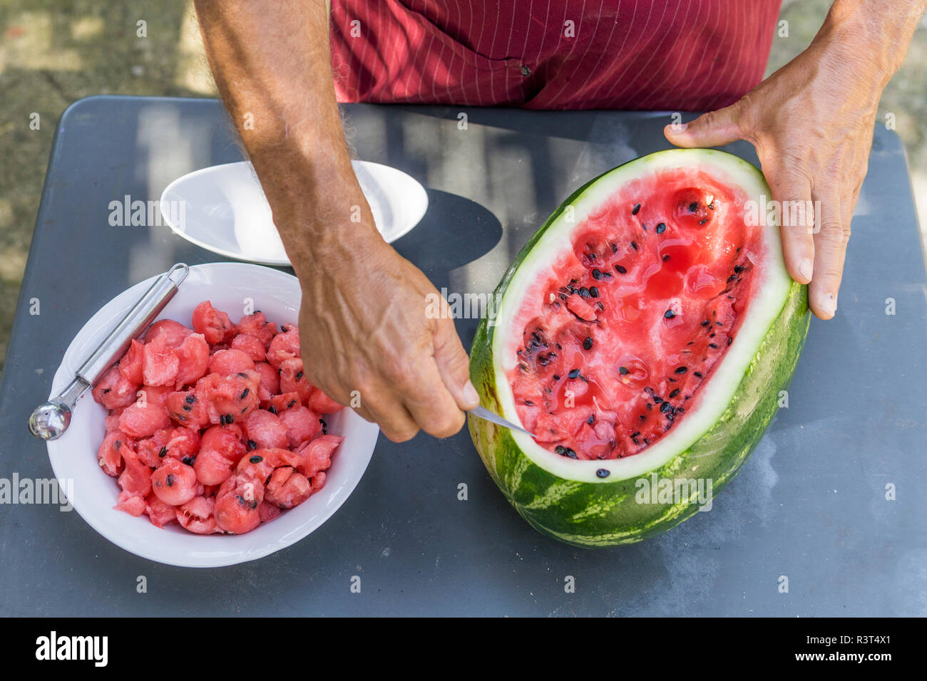 Close-up of man decorating a watermelon with carving tool - Stock Image