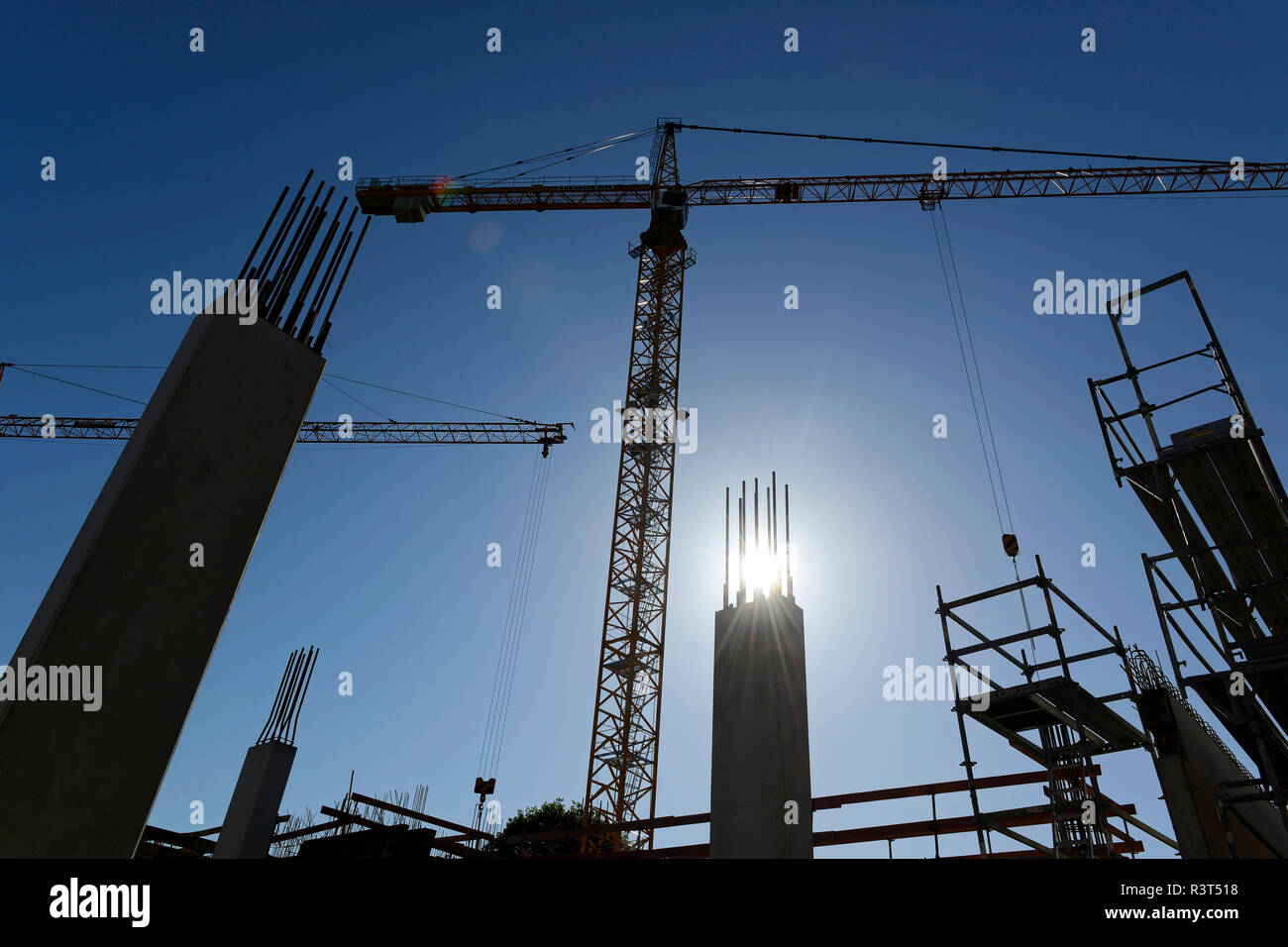 Germany, Bavaria, Geretsried, construction site, crane against the sun - Stock Image