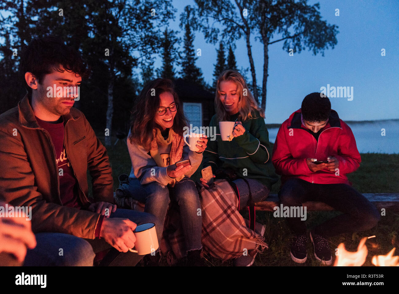 Group of friends sitting at a campfire, talking and drinking tea - Stock Image
