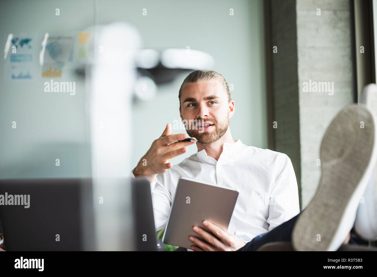 Young businessman sitting in office with feet up holding tablet and talking - Stock Image