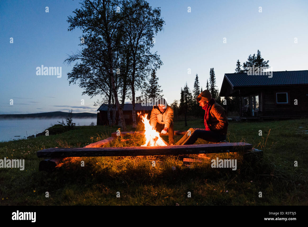 Friends sitting at a campfire, watching the flames - Stock Image