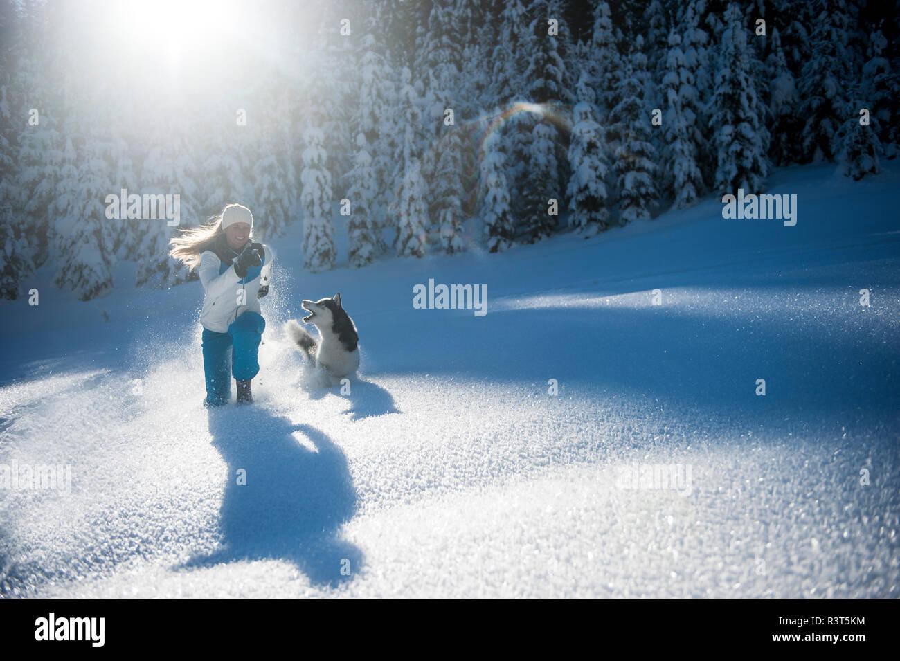 Austria, Altenmarkt-Zauchensee, happy young woman running with dog in snow - Stock Image