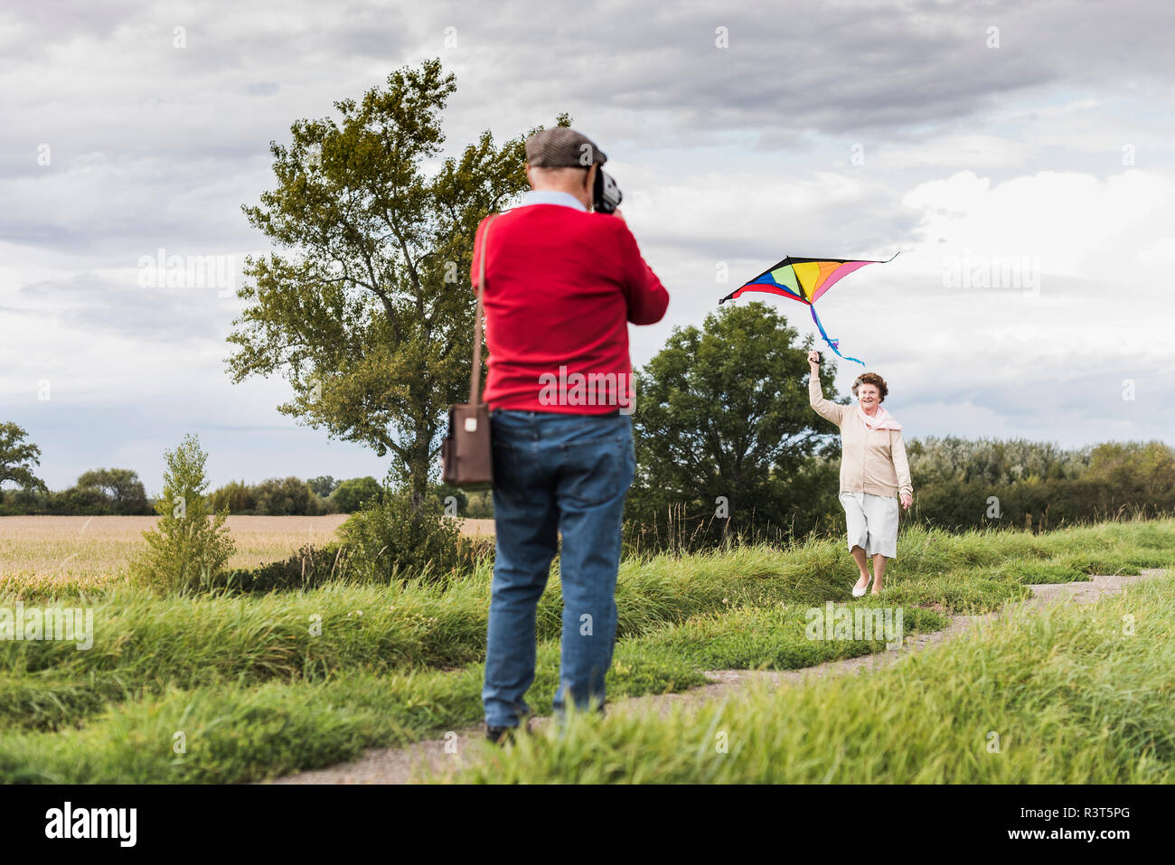 Senior man filming wife flying kite in rural landscape - Stock Image