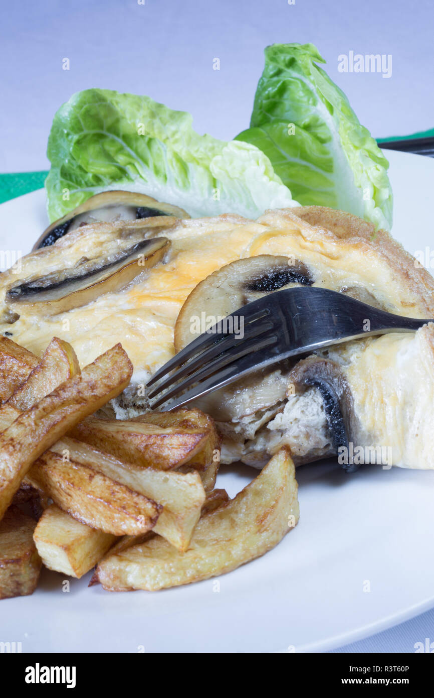 A plated meal of Mushroom omelette with chips/fries - Stock Image