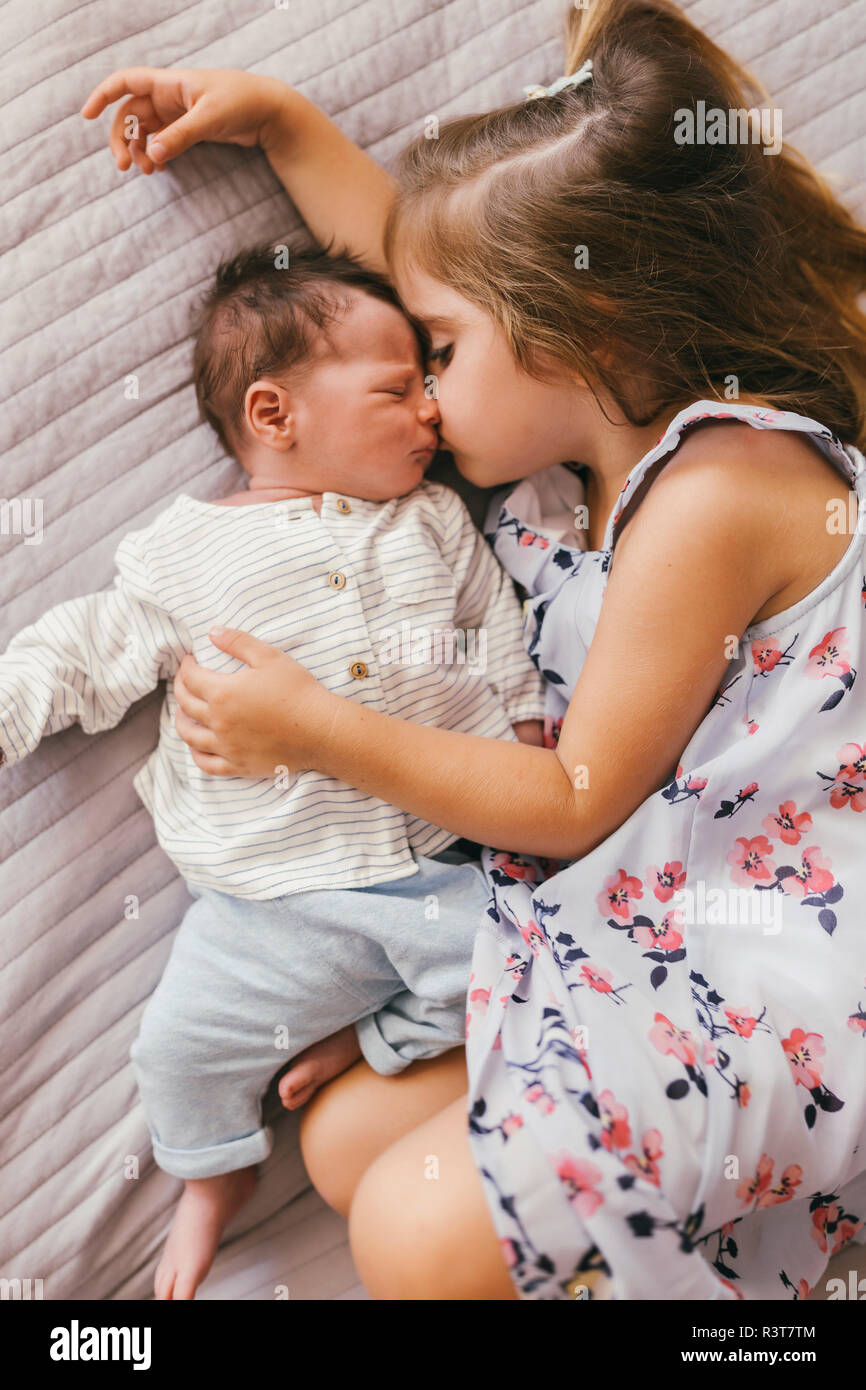 Affectionate girl lying on blanket cuddling with her baby brother - Stock Image