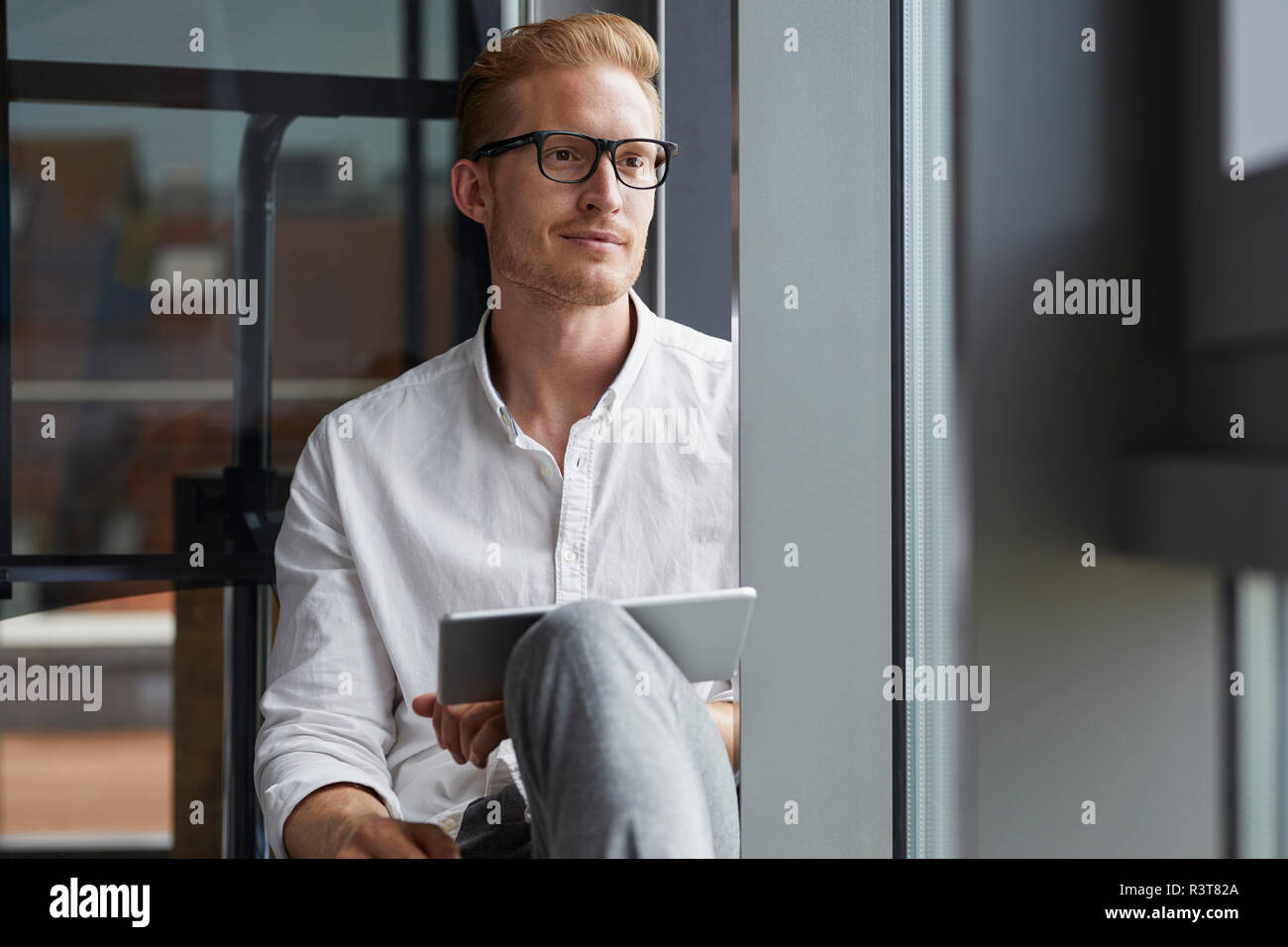 Smiling businessman sitting on windowsill with tablet - Stock Image