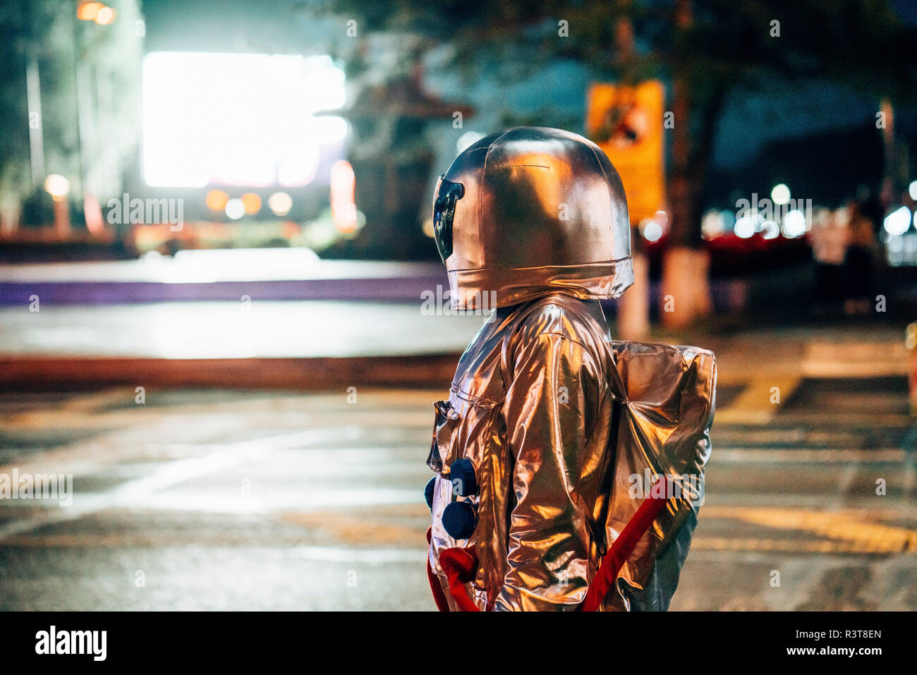 Spaceman on a street in the city at night attracted by shining projection screen Stock Photo