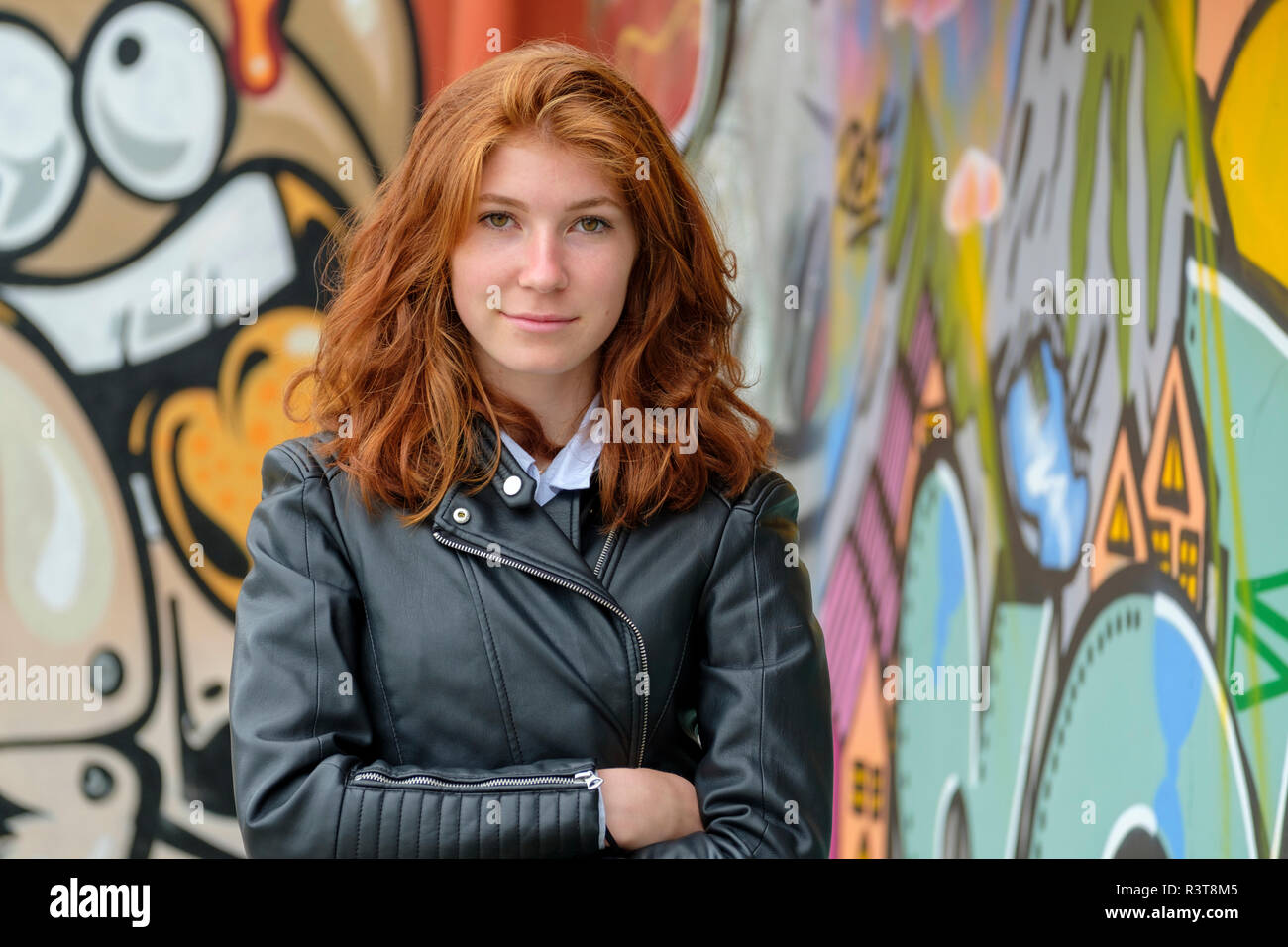 Italy, Finale Ligure, portrait of redheaded teenage girl wearing black leather jacket in front of mural - Stock Image