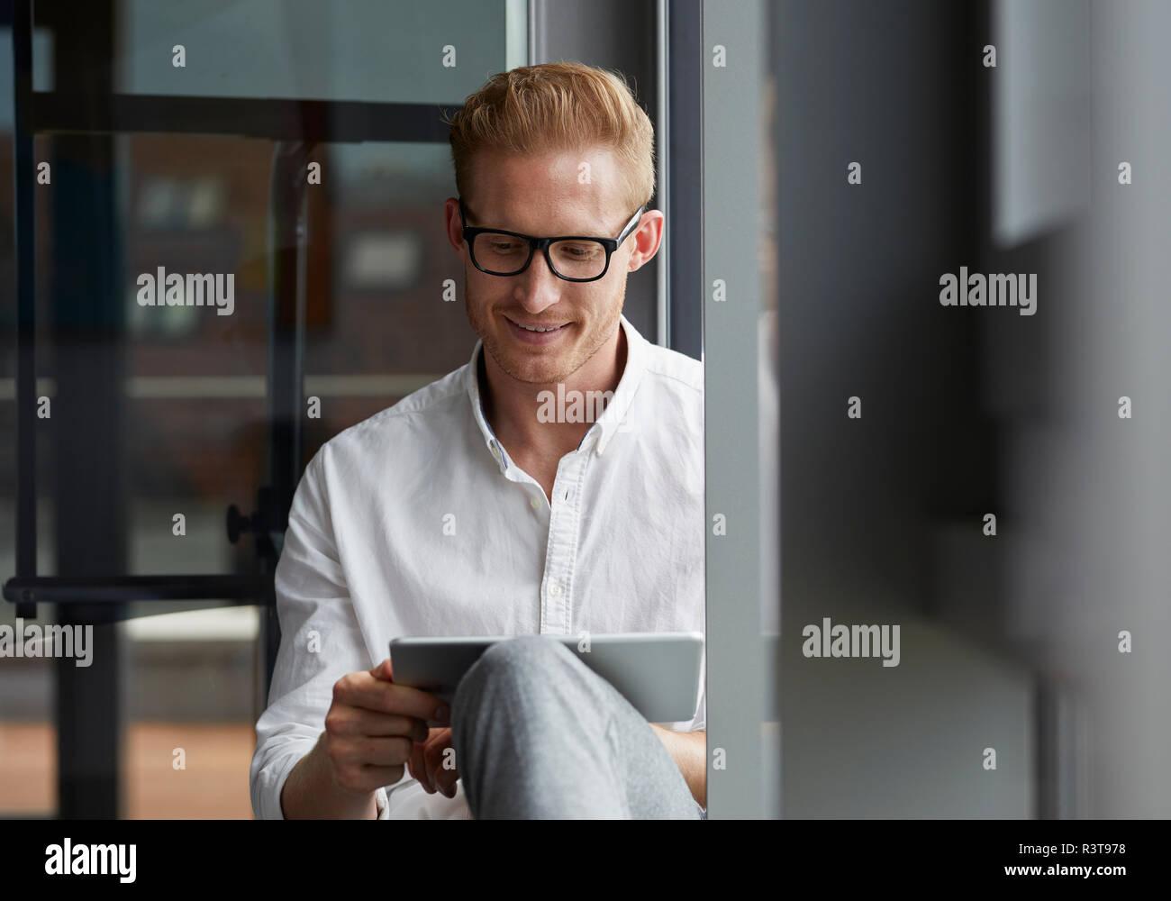 Smiling businessman sitting on windowsill using tablet - Stock Image