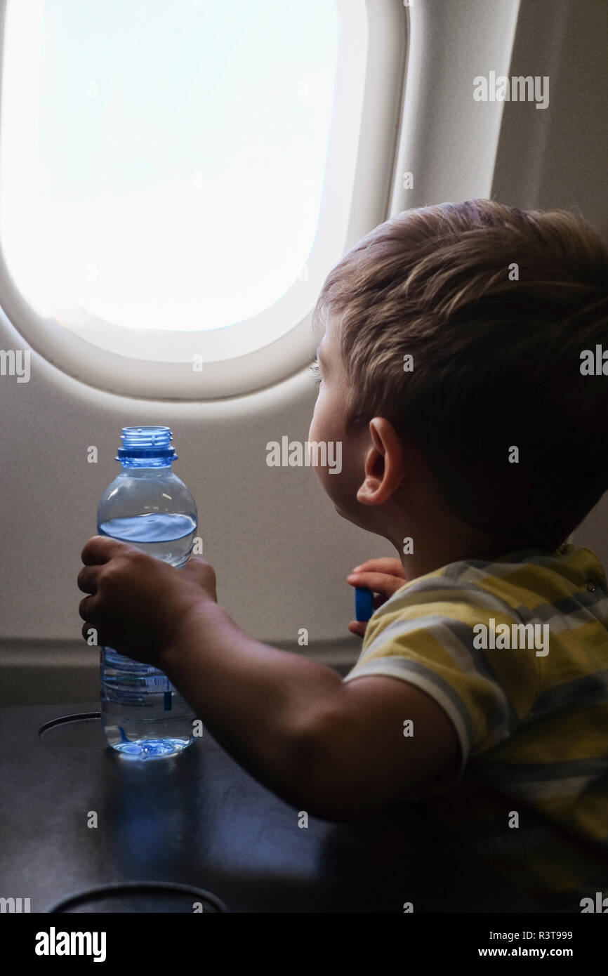 Little boy in an airplane looking out of window Stock Photo