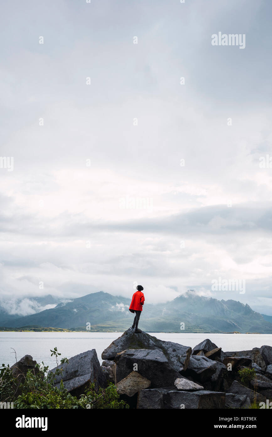 Norway, Senja island, rear view of man standing on a rock at the coast - Stock Image