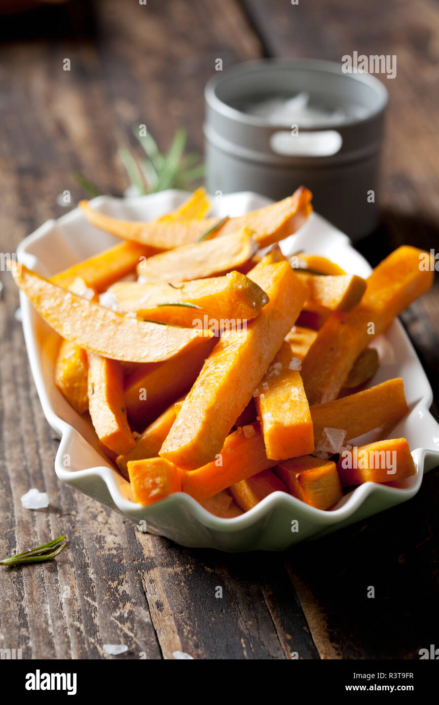 Sweet potato fries with rosmary and salt in porcelain bowl - Stock Image