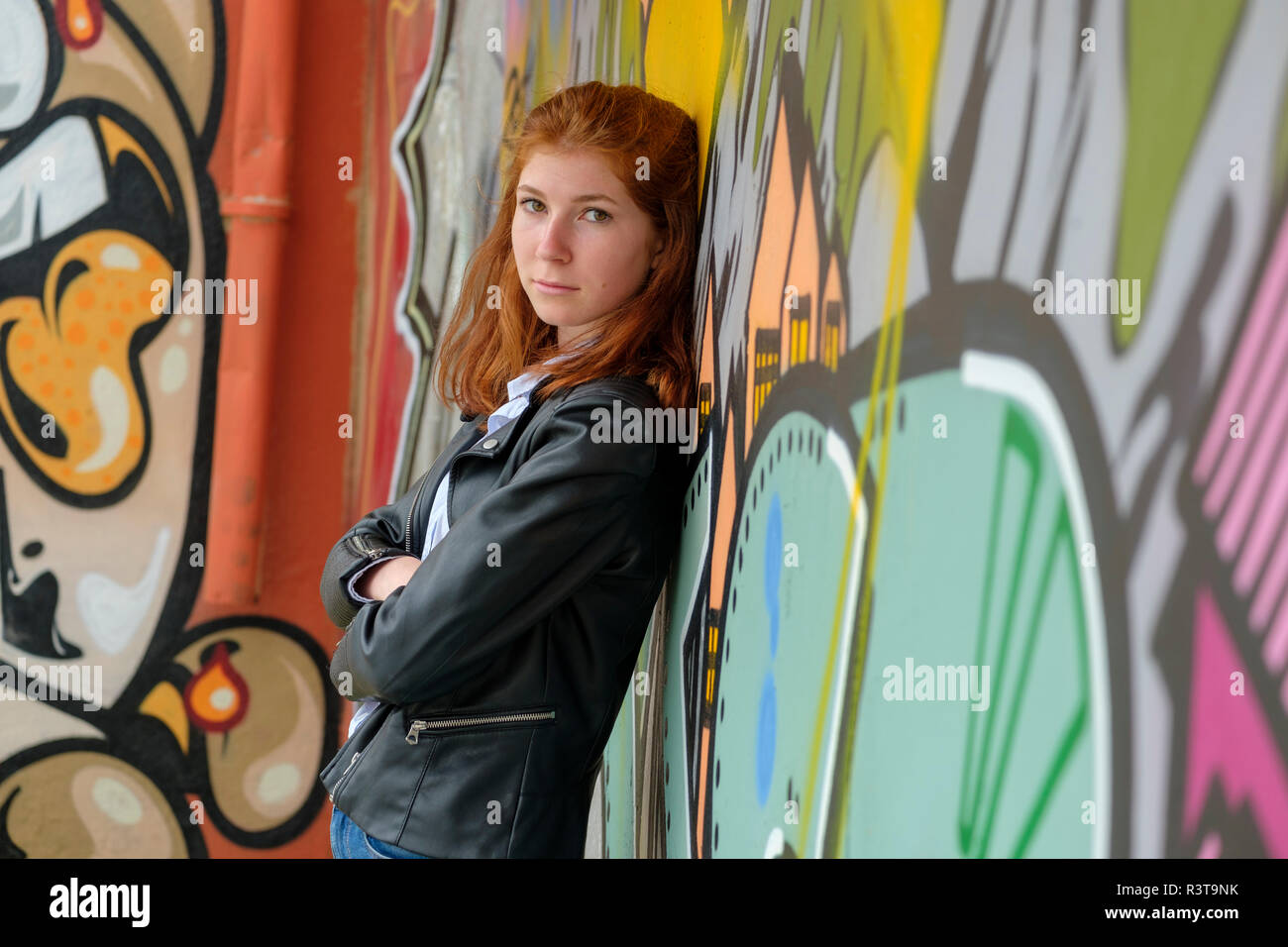 Italy, Finale Ligure, portrait of redheaded teenage girl leaning against mural - Stock Image