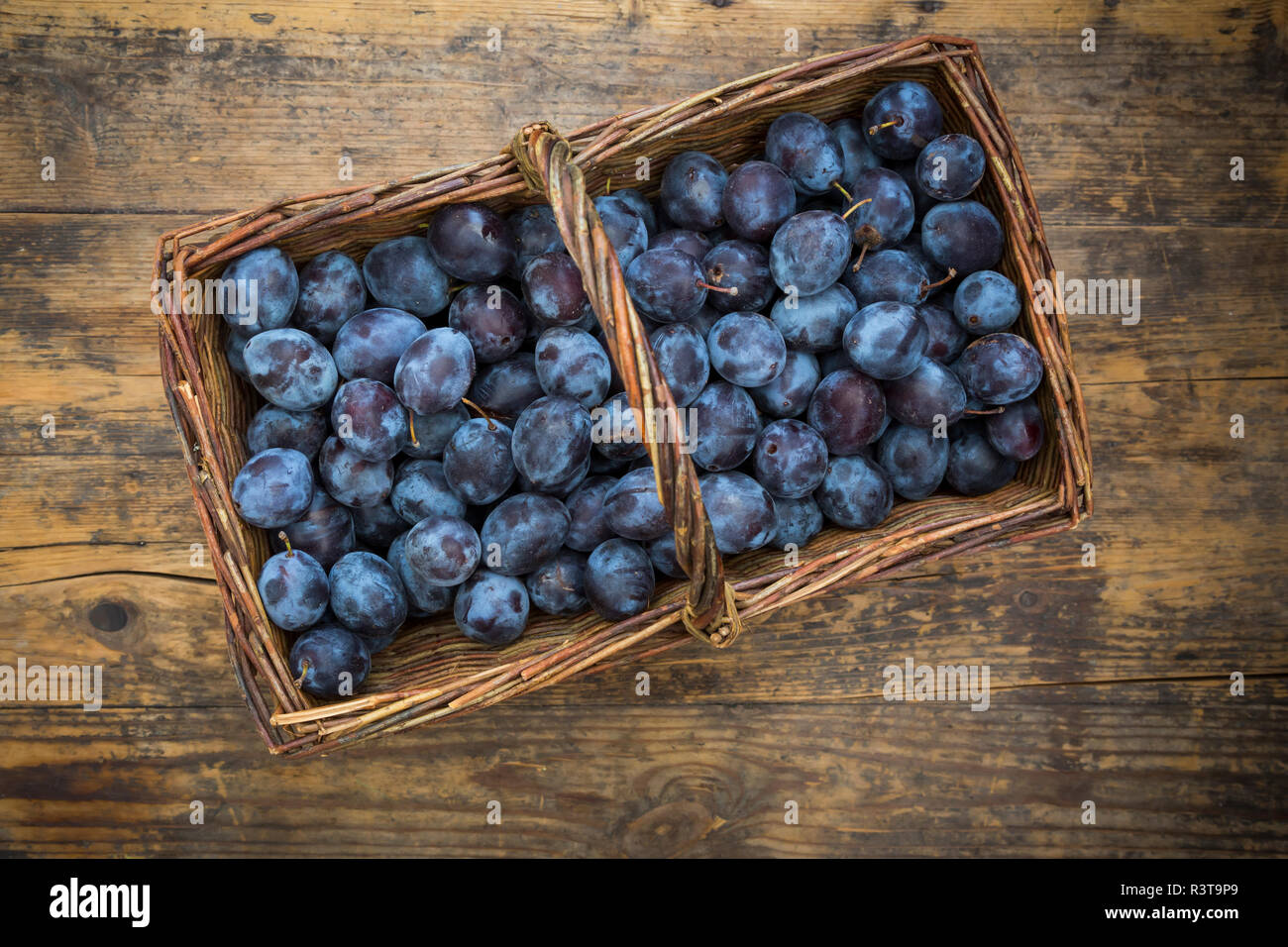 Wicker basket of organic plums, wooden table Stock Photo