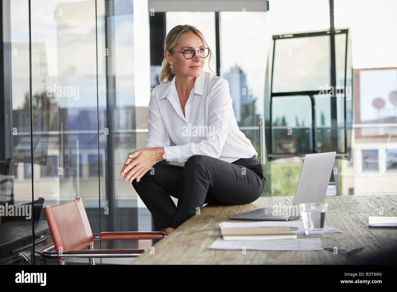 Successful businesswoman sitting on desk, contemplating - Stock Image