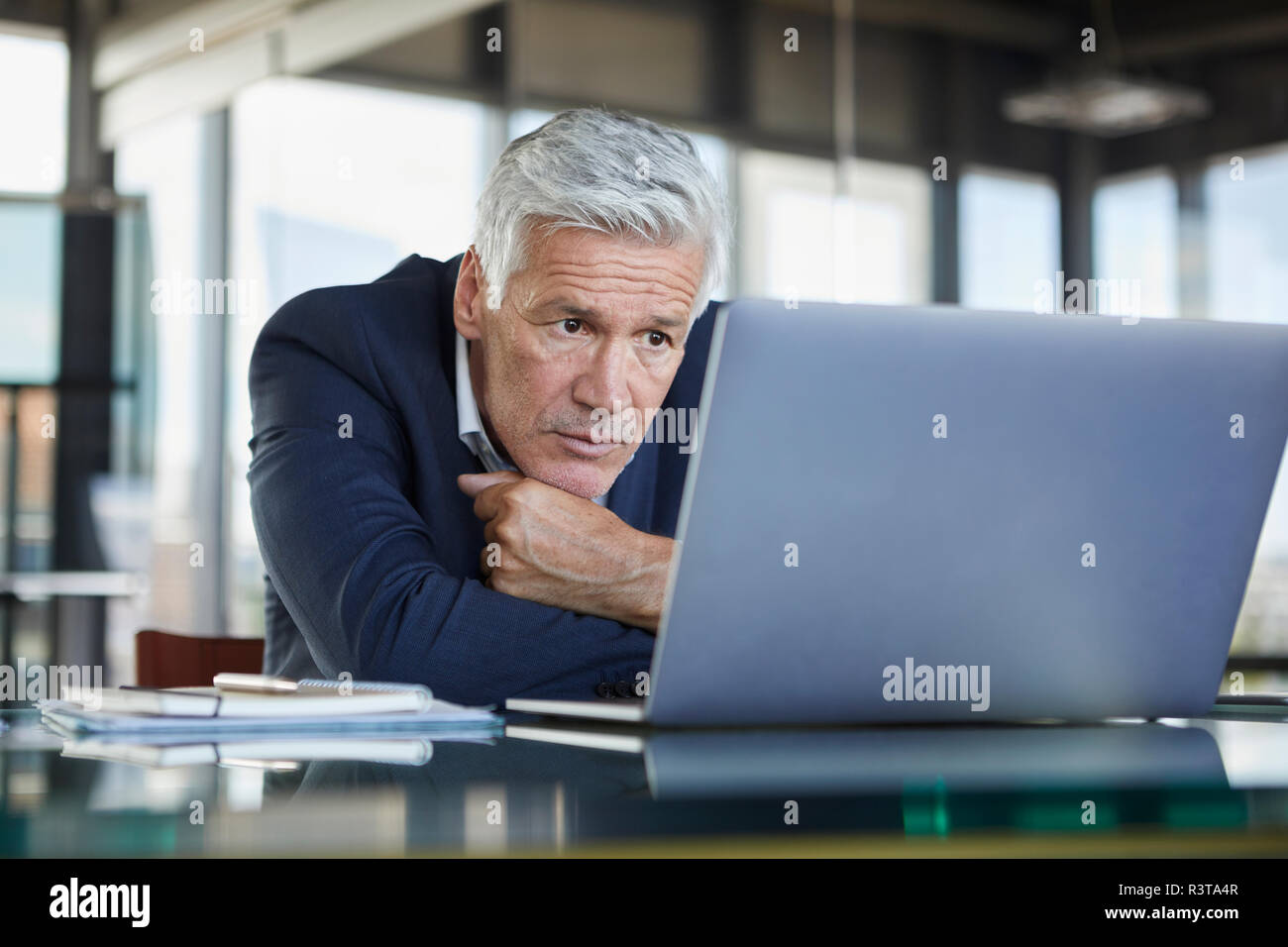 Businessman sitting at desk, trying to solve a problem - Stock Image