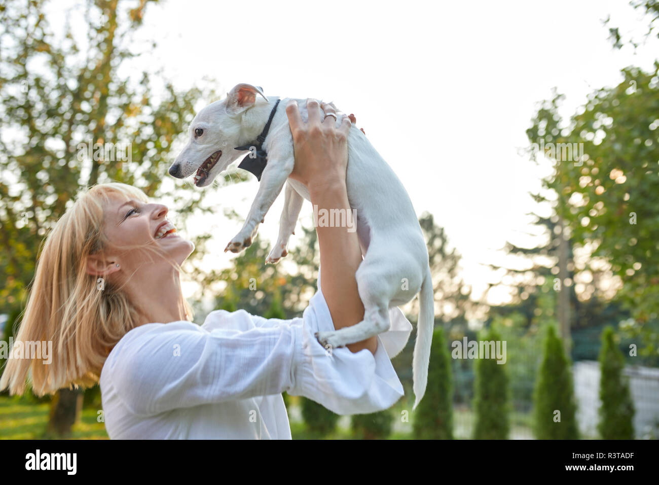 Happy woman holding dog wearing a bowtie outdoors - Stock Image