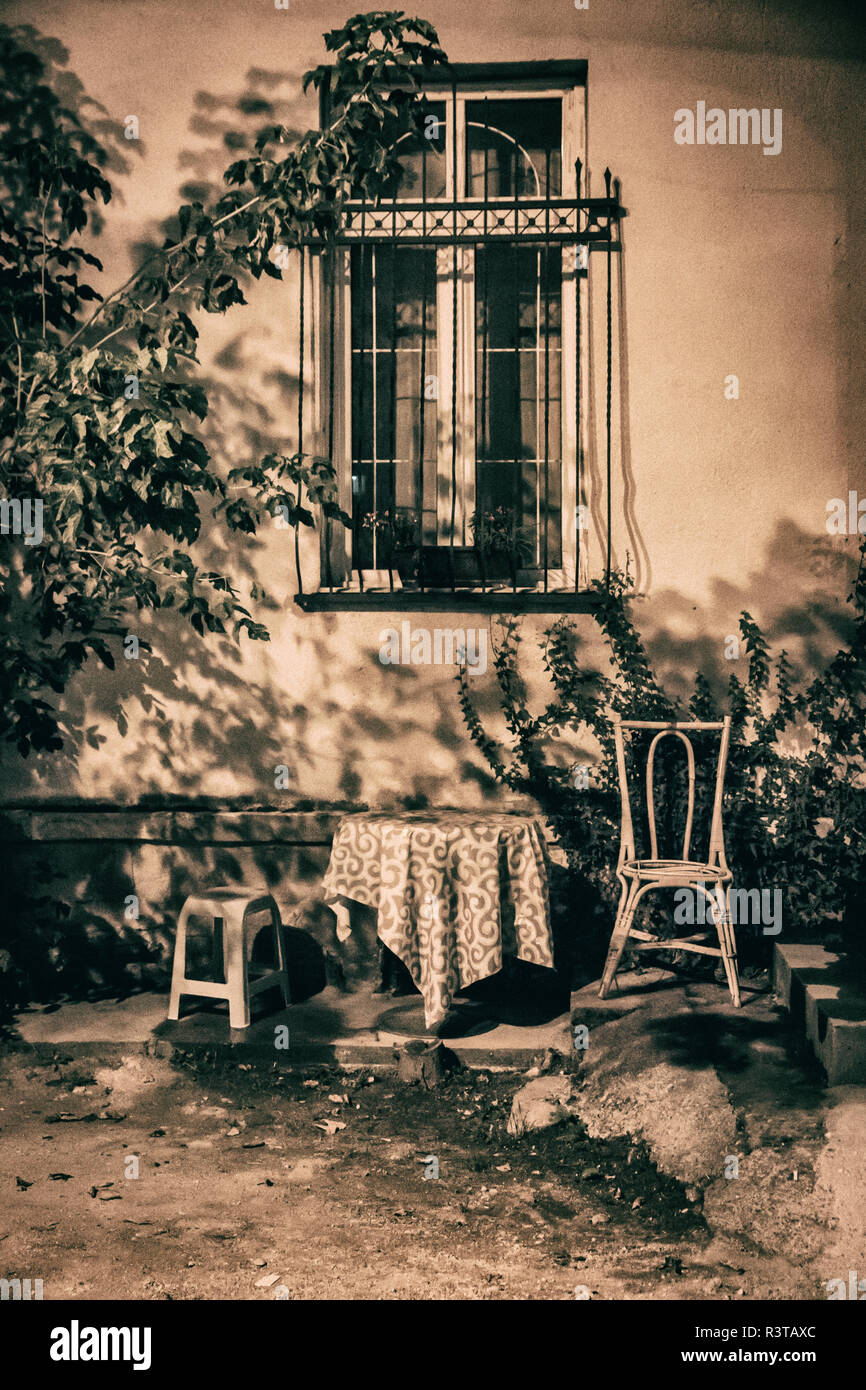 Southeast central Balkan Peninsula, The Macedonia, Skopje, evening along the Vadar river, table and chair. - Stock Image